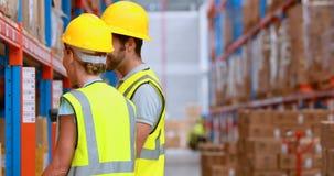 Mannelijke en vrouwelijke pakhuisarbeider het inspecteren voorraad stock videobeelden