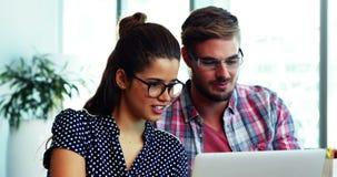 Mannelijke en vrouwelijke stafmedewerkers die over laptop bij bureau bespreken stock video
