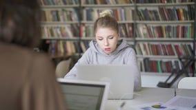 Mannelijke en vrouwelijke studenten die in de bibliotheek bestuderen stock footage