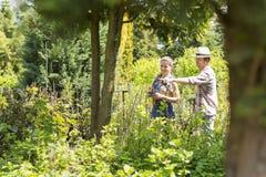 Mannelijke en vrouwelijke tuinlieden die over installaties bij installatiekinderdagverblijf bespreken Stock Foto