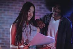Mannelijke en vrouwelijke uitvoerders die documenten in nachtclub lezen royalty-vrije stock afbeelding