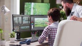 Mannelijke en vrouwelijke videoredacteurs die aan een project werken stock footage