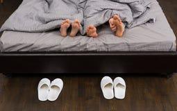 Mannelijke en vrouwelijke voeten, mensen` s hand die zijn voeten krassen onder grijs Royalty-vrije Stock Foto