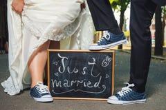 Mannelijke en vrouwelijke voeten in tennisschoenen Bruidbruidegom Huwelijk royalty-vrije stock fotografie