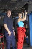 Mannelijke en vrouwelijke werktuigkundigen die aan auto werken Stock Foto