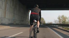Mannelijke fietser die een fiets berijden r Fietser die zwarte en rode uitrusting, helm en glazen dragen Sterke beenspieren stock video