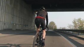 Mannelijke fietser die een fiets berijden r Fietser die zwarte en rode uitrusting, helm en glazen dragen Sterke beenspieren stock footage