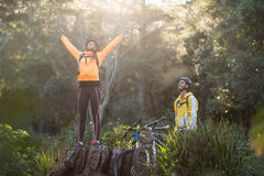 Mannelijke fietser die vrouwelijke fietser bekijken die zich met omhoog wapens bevinden Royalty-vrije Stock Foto
