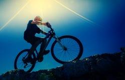 Mannelijke fietser op een backlit bergfiets, stock foto's