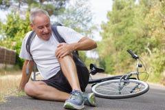 Mannelijke fietser worden die die na fietsongeval wordt verwond royalty-vrije stock foto