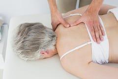 Mannelijke fysiotherapeut die de rug van een hogere vrouw masseren royalty-vrije stock foto