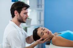 Mannelijke fysiotherapeut die hoofdmassage geven aan vrouwelijke patiënt Stock Afbeeldingen