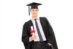 Mannelijke gediplomeerde die een diploma houden en tegen een muur leunen royalty-vrije stock foto's
