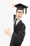 Mannelijke gediplomeerde student achter een paneel en het richten met vinger royalty-vrije stock foto's