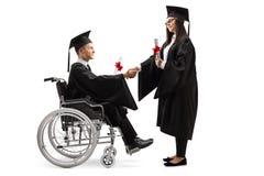 Mannelijke gediplomeerde student in een rolstoel die een hand met een vrouwelijke gediplomeerde student schudden royalty-vrije stock foto