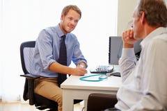 Mannelijke Geduldig Hebbend Overleg met Arts In Office stock foto