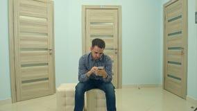 Mannelijke geduldige gebruikende telefoon terwijl het wachten op zijn artsenbenoeming Royalty-vrije Stock Foto
