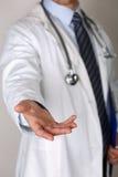 Mannelijke geneeskunde arts die helpend handclose-up aanbieden Stock Afbeeldingen