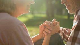 Mannelijke gepensioneerde die teder vrouwelijke hand op romantische datum in park, close-up houden stock videobeelden