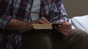 Mannelijke gevangene die heilig boek in gevangeniscel lezen, die naar antwoorden, het bidden zoeken stock footage