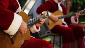 Mannelijke gitaristen die in Kerstmankostuums blije liederen spelen bij het overleg van de Kerstmisvooravond stock videobeelden