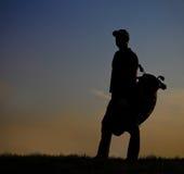 Mannelijke golfspeler bij zonsondergang Royalty-vrije Stock Afbeeldingen
