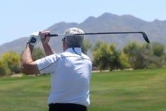 Mannelijke Golfspeler die een golfbal van een achtermening raken stock afbeelding