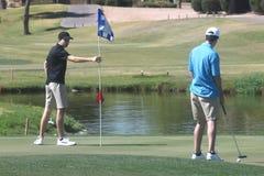 Mannelijke golfspelers bij groen zetten stock foto