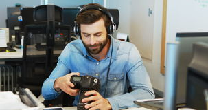 Mannelijke grafische ontwerper met hoofdtelefoons die camera met behulp van stock video