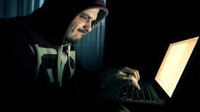 Mannelijke hakker in het kapwerk aangaande een computer stock footage