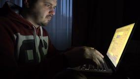 Mannelijke hakker in het kapwerk aangaande een computer stock videobeelden