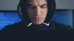 Mannelijke hakker in kap die aan een computer in een donkere bureauruimte werken Geschoten op Steadicam stock footage