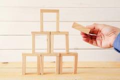 mannelijke hand de bouwtoren van domino houten blokken Royalty-vrije Stock Foto