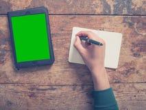 Mannelijke hand die in blocnote schrijven en tablet gebruiken Stock Afbeeldingen