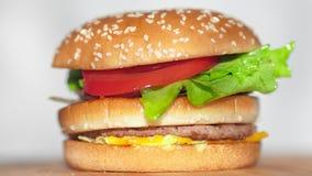 Mannelijke hand die die broodje zetten met sesam bovenop sappig smakelijk hamburgerclose-up wordt bestrooid stock videobeelden