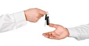 Mannelijke hand die een autosleutel houden en het overhandigen aan een andere perso Stock Fotografie