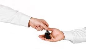 Mannelijke hand die een autosleutel houden en het overhandigen aan een andere perso Stock Foto's