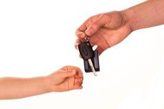 Mannelijke hand die een autosleutel houden en het overhandigen aan een andere persoon Stock Afbeelding