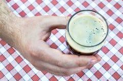 Mannelijke hand die een glas donker bier op een tafelkleed steunen royalty-vrije stock afbeelding