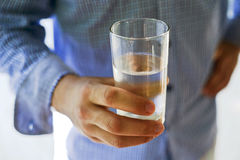 Mannelijke hand die een glas zoet water houden Stock Afbeelding