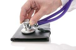 Mannelijke hand die een portefeuille met stethoscoop controleert Stock Foto