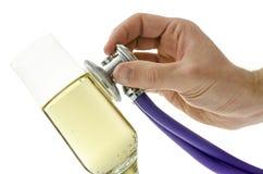 Mannelijke hand die een stethoscoop op een glas wijn houden Stock Afbeelding