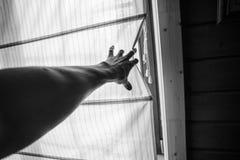 Mannelijke hand die een terug gordijn trekken royalty-vrije stock fotografie