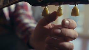 Mannelijke hand die elektrische gitaarclose-up stemmen stock video
