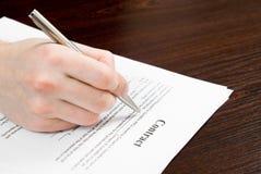 Mannelijke hand die en contract invult ondertekent Stock Foto's
