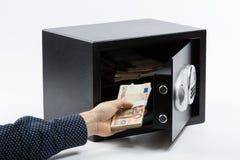 Mannelijke hand die euro bankbiljetten in een veilige stortingsdoos houden Stock Foto's