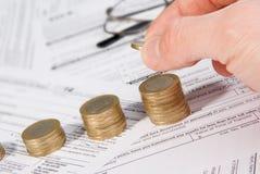 Mannelijke hand die geld bij het kweken van muntstukstapel zetten Stock Fotografie
