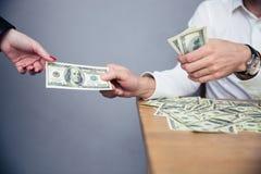 Mannelijke hand die geld geven aan vrouwelijke hand Stock Afbeeldingen