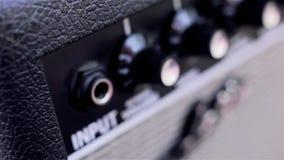 Mannelijke hand die in hefboomkabel aan gitaarversterker stoppen Close-up stock footage