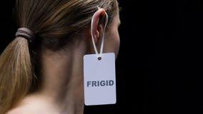 Mannelijke hand die ijzig etiket op vrouwelijk oor hangen, vernederend persoonlijkheid, inbreuk stock videobeelden